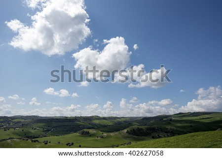 blue sky and clouds on green lanscape - stock photo