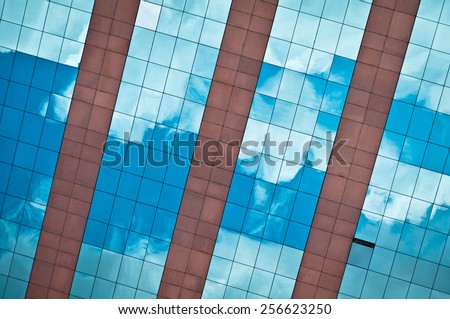 Blue Sky and Clouds Reflected in Modern Business Building Glass Facade - stock photo