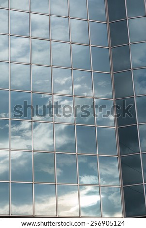 Blue Sky and Clouds Reflected in the Glass Building - stock photo