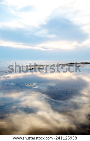 Blue sky and clouds reflected on the water of a tranquil seashore for summer vacation concept. - stock photo