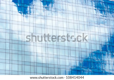 Blue sky and clouds reflecting on a building with mirrored glass - stock photo