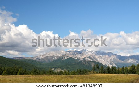 Blue sky and cumulus clouds over the Eastern Sayan Mountains and Mount MunKu-Sardyk. Photo partially tinted.