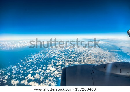 Blue sky and engine. View from window of airplane flying in clouds. Skyscape cloudscape. Bird's eye. - stock photo