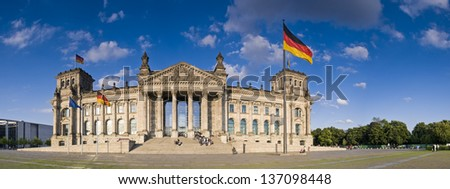 Blue sky and German flags flying over the Reichstag, Berlin's parliament built 1894. Perspective corrected stitched panorama detailed when viewed large. - stock photo