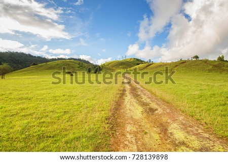 Blue sky and grass mountains and light green grass