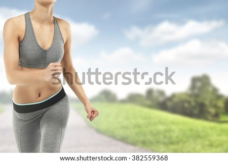 blue sky and green grass with woman on road and slim body