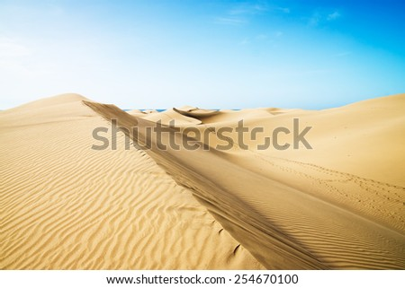 Blue sky and sand dunes with footprints. Canary islands, Maspalomas. Spain.