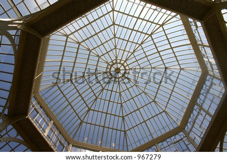 Blue sky and sun gleaming through greenhouse/orangery roof - stock photo