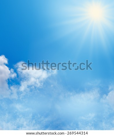 Blue Sky and Sunshine Background   Big bright sunburst in right top corner, large copy space on left side with soft fluffy clouds in bottom third of image and more copy space - stock photo