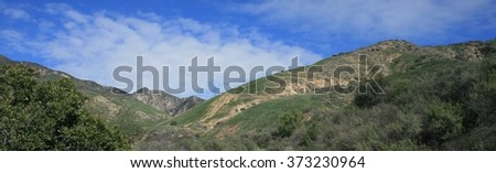 Blue sky and white clouds above green hills, California - stock photo