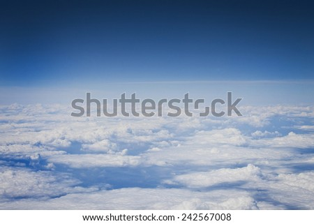 Blue sky and white clouds viewed above. - stock photo