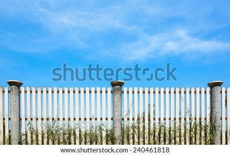 Blue sky and wood fence horizon with grass