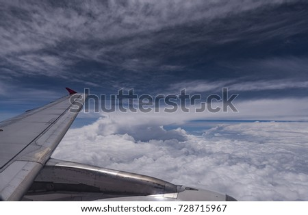 Blue sky background with white cloud viewed from airplane windows