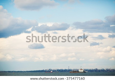 Blue sky background with white clouds and sea line with ships. Blue clear sky panorama with vessels. - stock photo