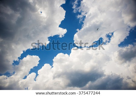 Blue sky background with white clouds. Blue clear sky panorama with contrast cloud closeup. - stock photo