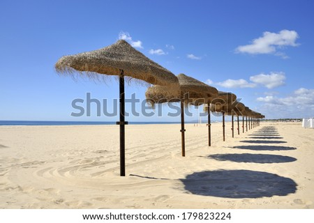 Blue sky, blue sea and parasols at Montegordo beach in Portugal  - stock photo