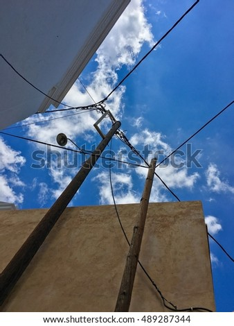 Blue sky. Chaotic power lines in Greece.