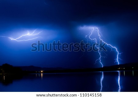 Blue sky Cloud to Cloud and cloud to ground Lightning striking the Colorado front range foothills with a reflection in the water of a lake. - stock photo