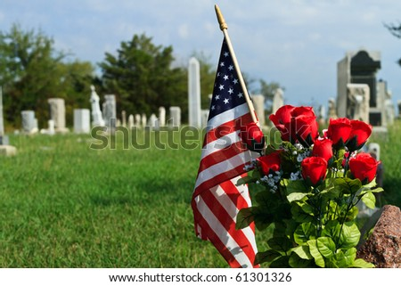 Blue sky, green grass, American Flag and graveyard