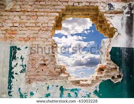 blue sky in a hole on a background an old wall - stock photo