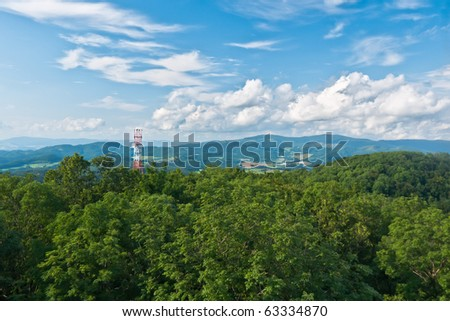 Blue sky in contact with the transmitter protuberant above forest - stock photo