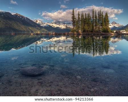 Blue sky over amazingly clear mountain lake with a symmetrical reflection - stock photo