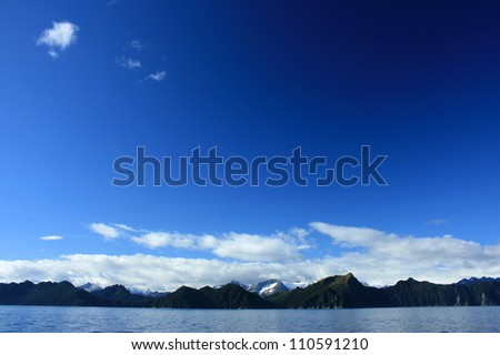 Blue Sky over Mountains and Fjord in Kenai Fjords National Park, near Seward, Alaska, USA - stock photo