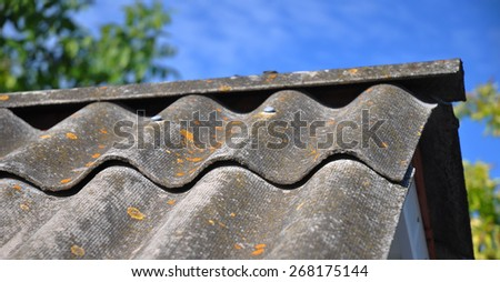 Blue sky over the dangerous asbestos old roof tiles able to use as background.  - stock photo