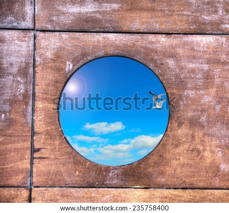 blue sky seen through a porthole. Processed for hdr tone mapping effect. - stock photo