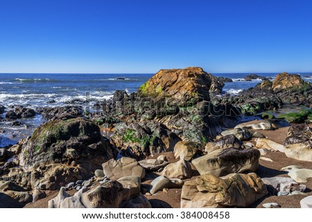 Blue sky, tidal pools, rock and geological formations along the rugged Big Sur coastline, near Monterey, CA. on the California Central Coast. - stock photo