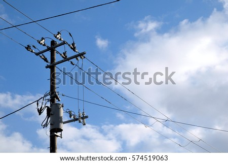 Blue sky,utility pole,electric wires.