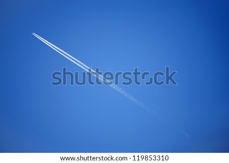 Blue sky with a long trail of jet - stock photo