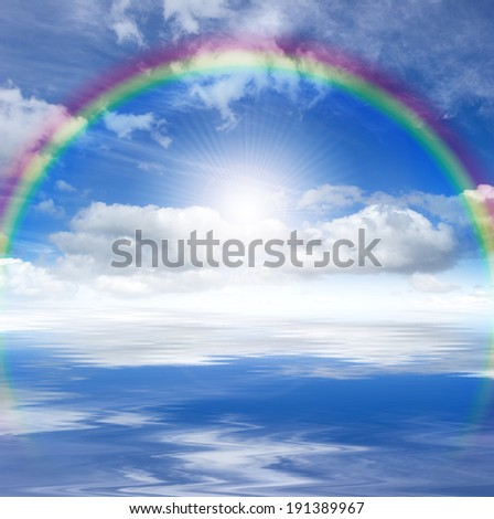 Blue sky with bright sun, rainbow and clouds, reflected in a water