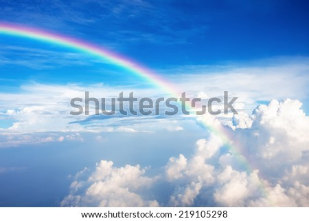Blue sky with clouds and a rainbow - stock photo