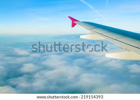 Blue sky with clouds and aircraft wing view from airplane.