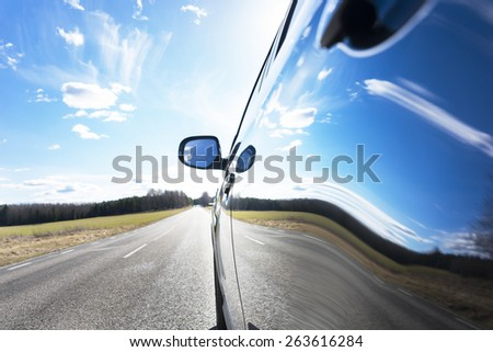 Blue sky with clouds and asphalt road reflected in side of car  - stock photo
