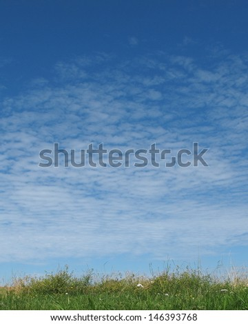 Blue sky with clouds and green grass - stock photo