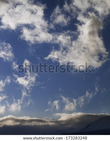 Blue sky with clouds and mountains at evening. Caucasus Mountains, Georgia, ski resort Gudauri. - stock photo