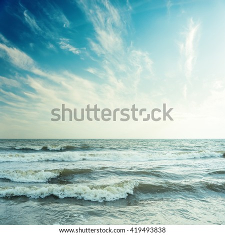 blue sky with clouds and stormy sea in sunset - stock photo
