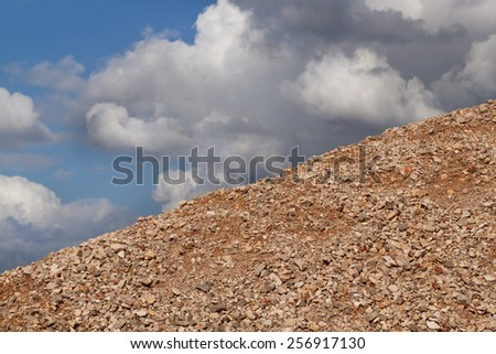 Blue sky with clouds and the mountain of gravel - stock photo