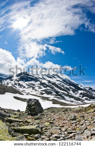 blue sky with clouds over rocky landscape in Norway - stock photo