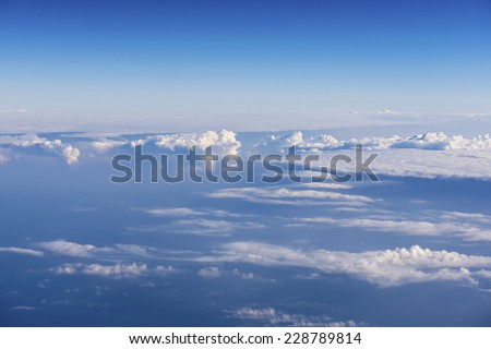 Blue sky with clouds. The shot taken from a airplane. - stock photo