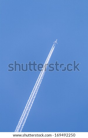 blue sky with condensation trail of aircraft