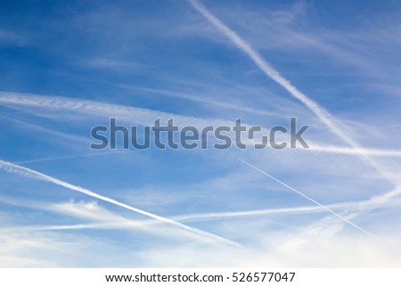 Blue sky with contrails and clouds, for use as background or for copy or text.
