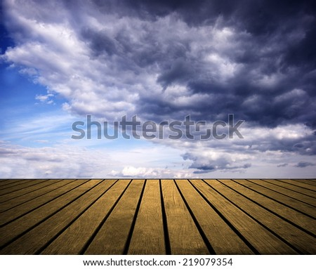 Blue sky with dark clouds and wood planks floor background  - stock photo