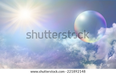 Blue sky with fluffy delicately color tinted clouds and a vibrant sunburst on left side with a large rainbow colored transparent bubble on right side - stock photo