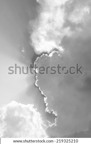Blue sky with sunbeams and clouds in black and white.  - stock photo