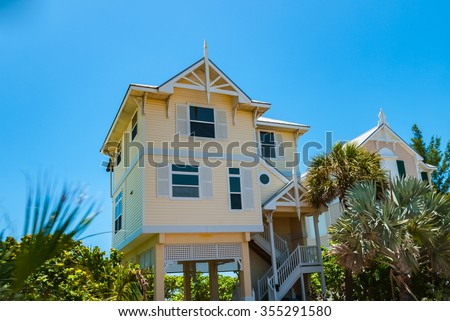 Blue sky with typical beach house in Florida Keys USA  Colorful residential buildings along the road to Key West on a sunny summer day behind green palm trees - stock photo