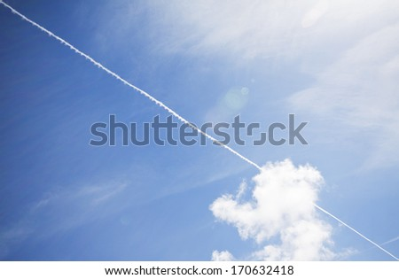 Blue sky with vapor trails from a plane - stock photo