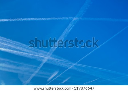 blue sky with vapor trails from planes that intersect and are parallel